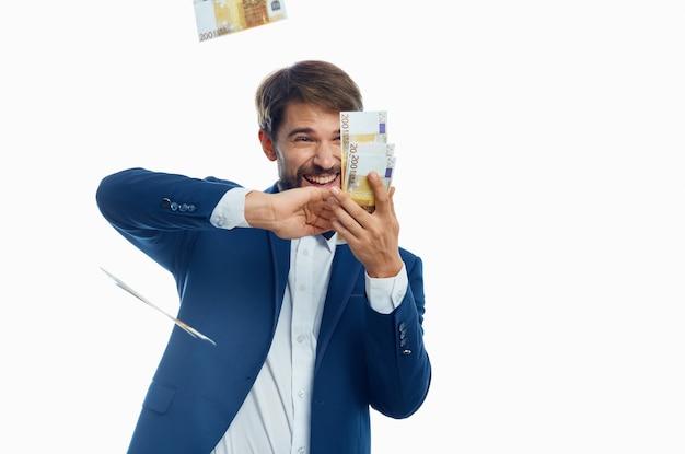 De gelukkige mens verspreidt geld op lichte achtergrondkostuummodel bedrijfsfinanciën.