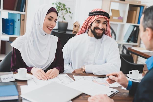 De gelukkige mensen ondertekenen contract arabisch paar bij makelaar in onroerend goed.