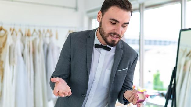 De gelukkige mensenbruidegom houdt een trouwring in de manierkleding van de huwelijksbruid