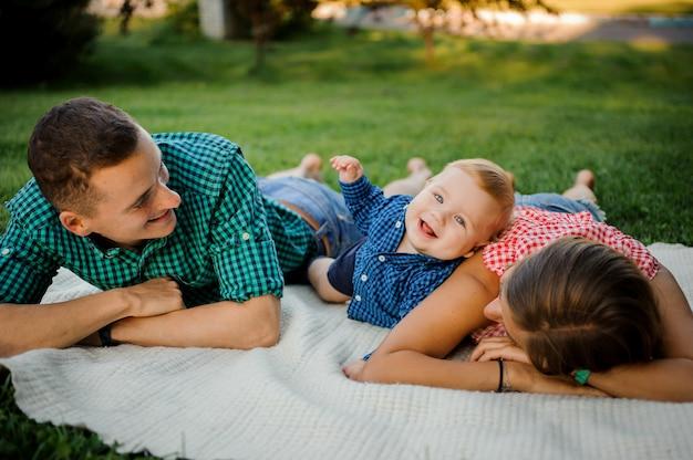 De gelukkige moeder, de vader en de zoon kleedden zich in de geruite overhemden die op de plaid in het park liggen