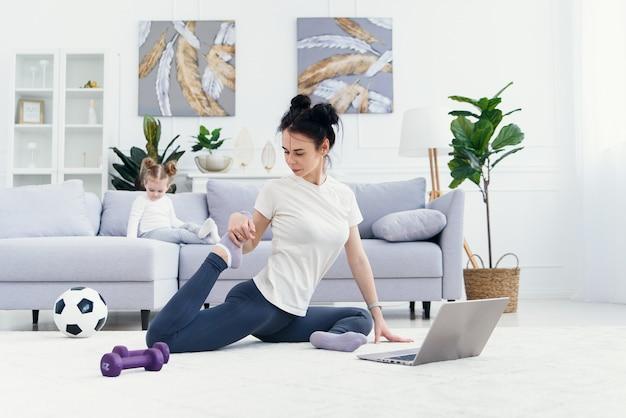 De gelukkige moeder die ochtendoefeningen in yoga doen stelt terwijl haar weinig dochter die thuis spelen. jonge schattige moeder plezier beoefenen van meditatie ontspannen op stressvrij weekend met babymeisje.