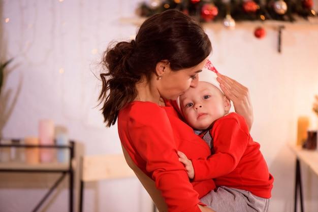 De gelukkige moeder en de aanbiddelijke baby in kerstmanhoed vieren kerstmis. nieuwjaars vakantie. peuter met moeder in de feestelijk ingerichte kamer