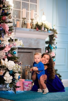 De gelukkige moeder en de baby vieren kerstmis. nieuwjaars vakantie.