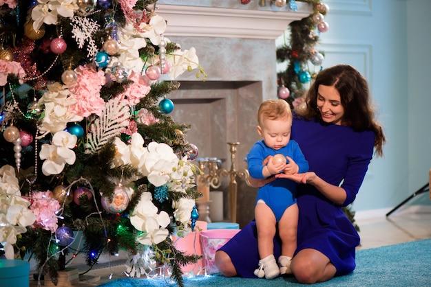 De gelukkige moeder en de baby vieren kerstmis