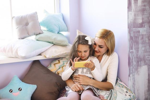 De gelukkige moeder en de dochter letten op smth op smartphone en zitten dichtbij het venster in de heldere ruimte