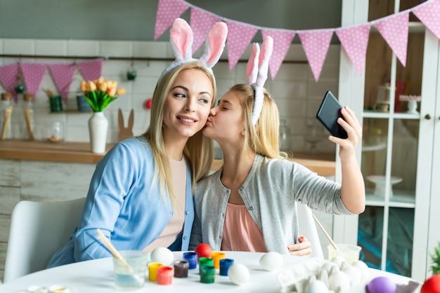 De gelukkige moeder en de dochter nemen een foto selfie dragend in konijntjesoren. voorbereiding op pasen