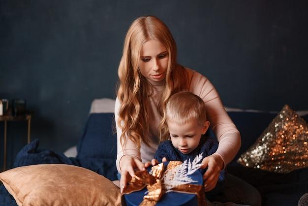 De gelukkige moeder en de zoon openen de giftdoos