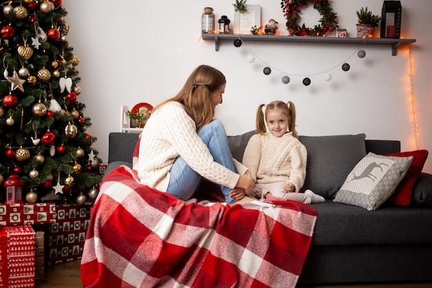De gelukkige moeder en het meisje van de familievrouw ontspannen thuis dichtbij kerstboom