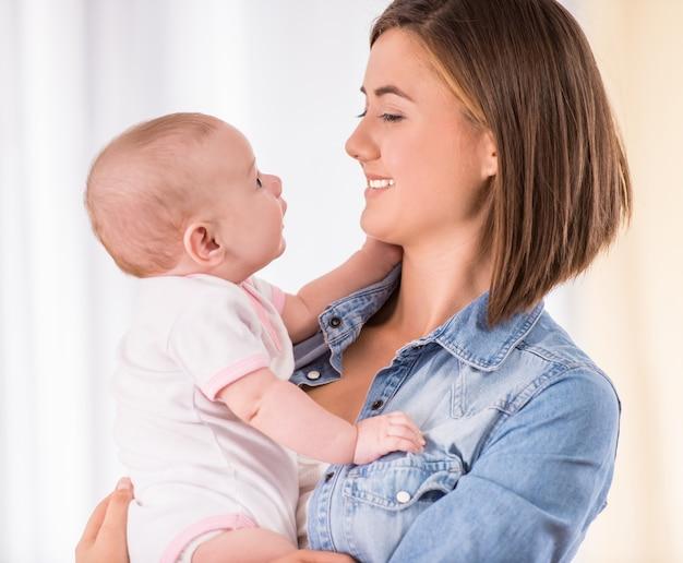De gelukkige moeder houdt babymeisje en bekijkt haar.