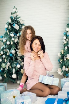 De gelukkige moeder met dochter die kerstmis deelt stelt op het belangrijkste plan voor.