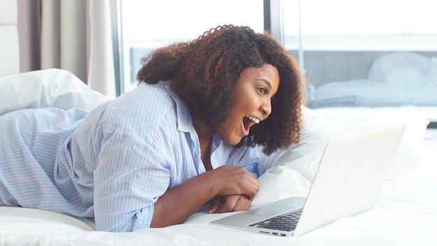 De gelukkige mollige afrikaanse jonge vrouw babbelt online met haar familie terwijl liggend in bed. quarantaine vanwege de pandemie