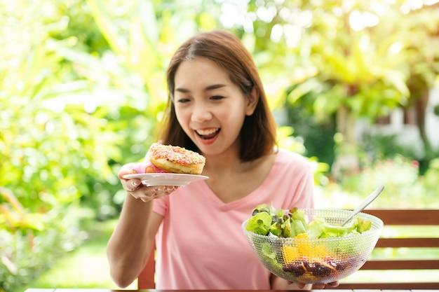 De gelukkige mooie aziatische gezonde vrouwenzitting van middelbare leeftijd op het balkon