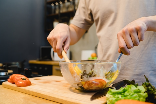 De gelukkige mooie aziatische mens bereidt saladevoedsel in de keuken voor
