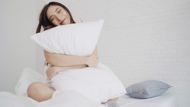 De gelukkige mooie aziatische vrouw ontwaakt, glimlacht en uitrekt haar wapens in haar bed in de slaapkamer.