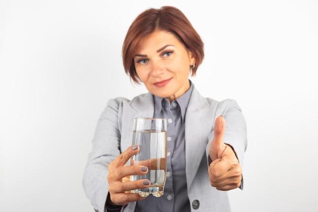 De gelukkige mooie bedrijfsvrouw biedt een glas water aan. dorst en gezondheid.