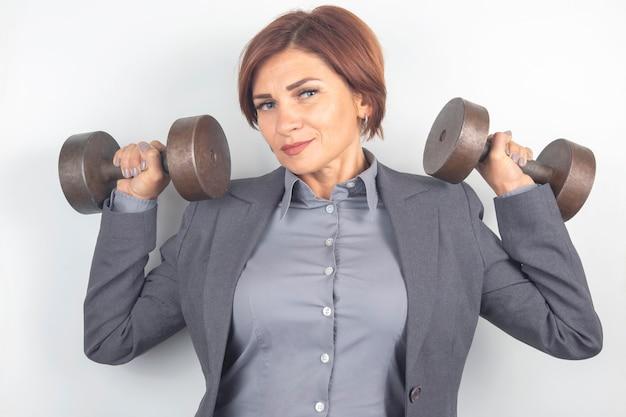De gelukkige mooie bedrijfsvrouw in een kostuum heft domoren op een witte achtergrond op. fitness en gezondheid. carrièregroei en werk