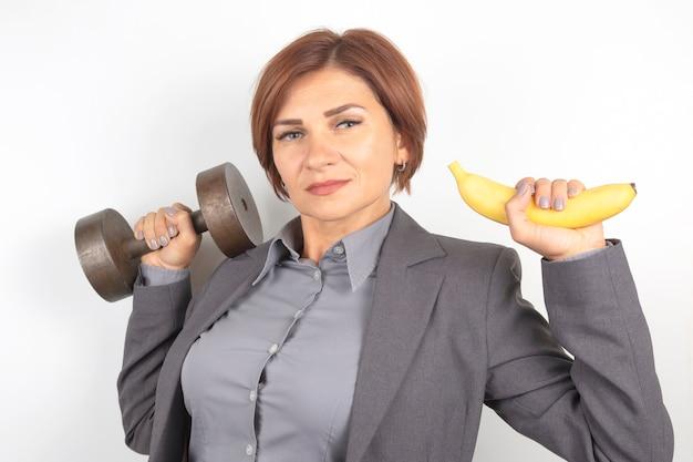 De gelukkige mooie bedrijfsvrouw in een kostuum heft een domoor en een banaan in haar handen op. fitness en gezondheid. goede voeding en uitstekende resultaten.