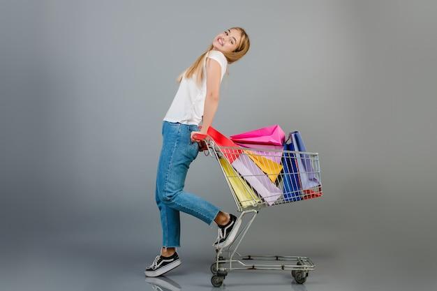 De gelukkige mooie blondevrouw heeft handkar met kleurrijke die het winkelen zakken over grijs worden geïsoleerd