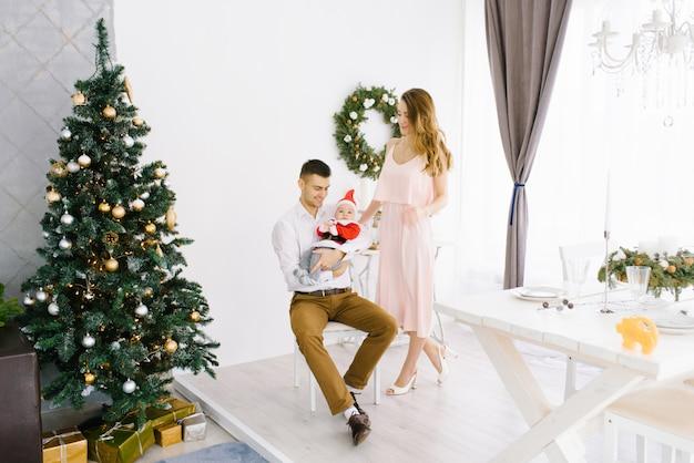 De gelukkige mooie familie met baby in klein kerstmankostuum viert kerstmis