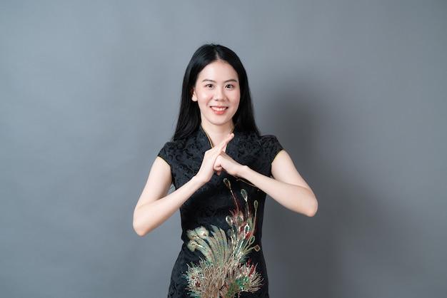 De gelukkige mooie jonge aziatische vrouw draagt zwarte chinese traditionele kleding op grijze oppervlakte