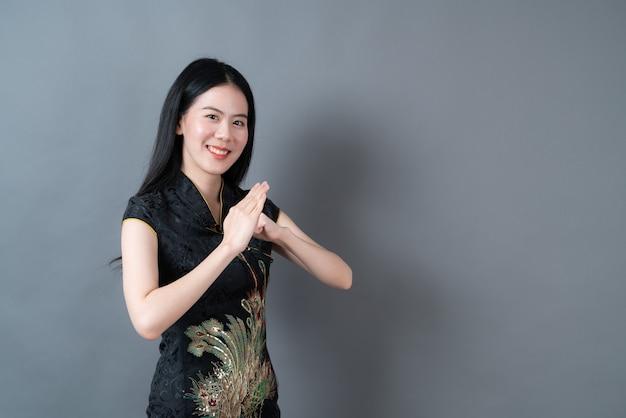 De gelukkige mooie jonge aziatische vrouw draagt zwarte chinese traditionele kleding
