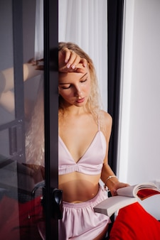 De gelukkige mooie jonge blonde vrouw met krullend haar in slaap draagt lingerie-ondergoed, lichtroze bustehouder en korte broek
