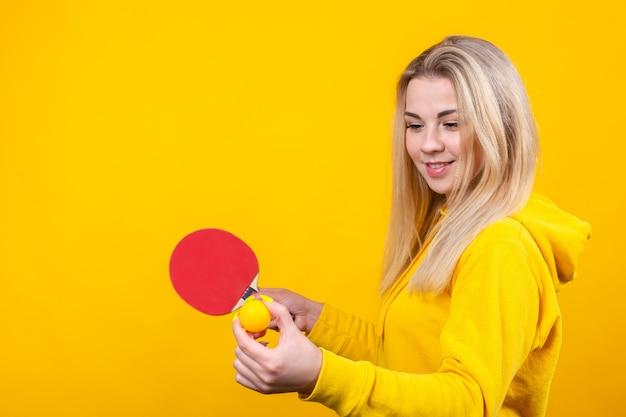 De gelukkige mooie jonge blondevrouw in toevallige gele sportieve kleren spelen pingpong, houdend een bal en een racket.