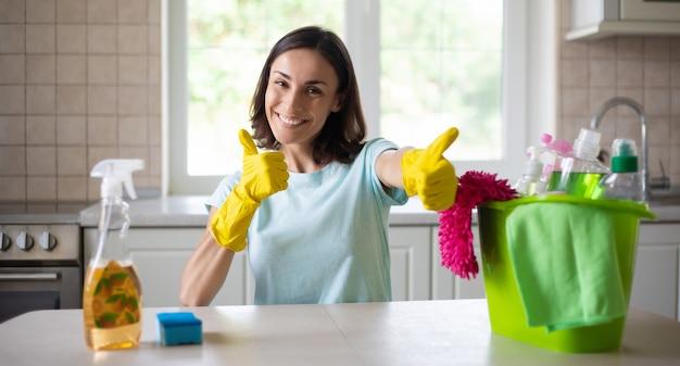 De gelukkige mooie jonge vrouw in gele handschoenen maakt de keuken schoon met speciaal materiaal en nevel