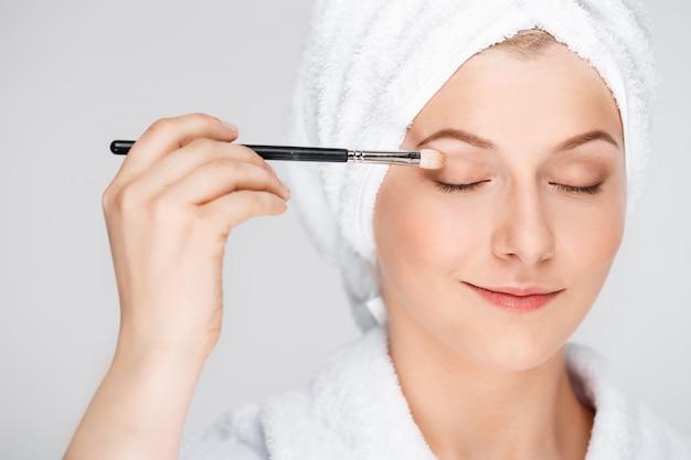 De gelukkige mooie vrouw past make-up met borstel toe, draagt badhanddoek