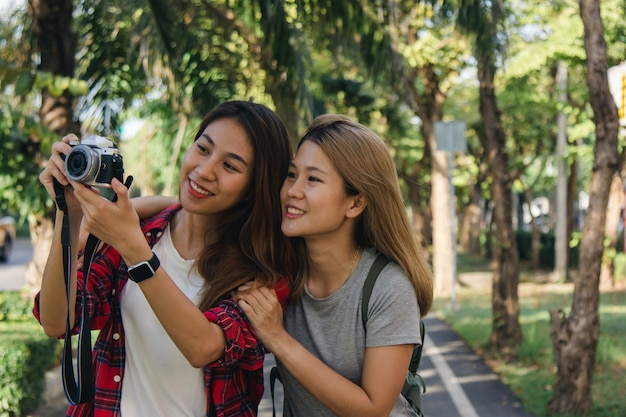 De gelukkige mooie vrouwen van de reizigers aziatische vriend dragen rugzak