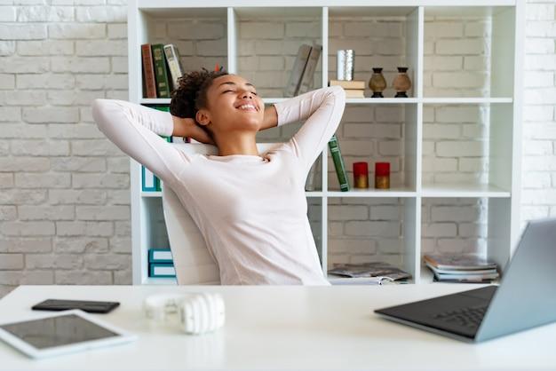 De gelukkige mulatvrouw heeft een pauze in het kantoor, vouwde armen bij het hoofd en lag de stoel omhoog kijkend