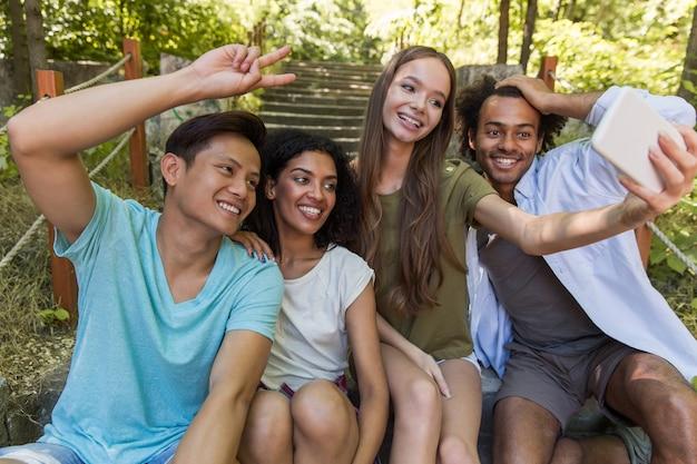 De gelukkige multi-etnische vriendenstudenten maken in openlucht selfie