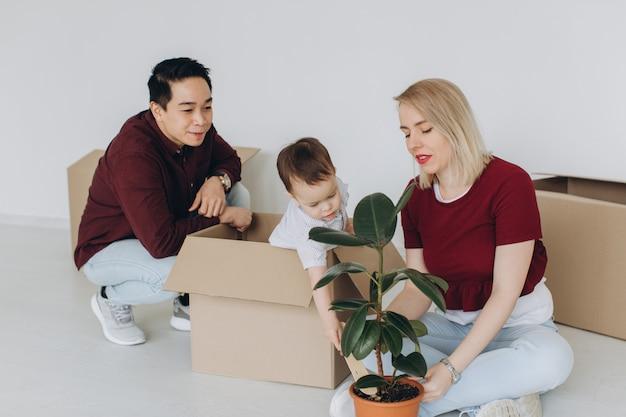 De gelukkige multiculturele familie, de aziatische vader en de kaukasische moeder met hun zoontje pakken dozen in nieuw huis uit. nieuwbouw woonhuis aankoop appartement concept.