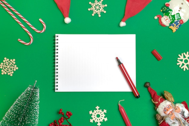 De gelukkige nieuwjaarvlakte legt samenstelling, blocnote, plaats voor het decor van tekstkerstmis, groene kleur