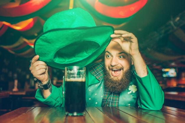 De gelukkige opgewekte jonge mens in groen kostuum zit bij lijst in bar. hij houdt de hoed boven een mok donker bier. jonge man glimlach.