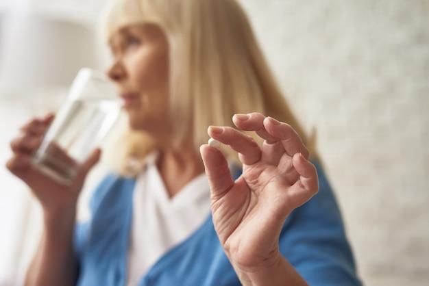 De gelukkige oude vrouw die ochtendpillen nemen drinkt water.