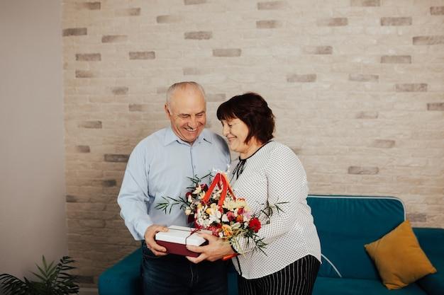 De gelukkige oudere man geeft bloemen en een geschenk aan zijn vrouw.