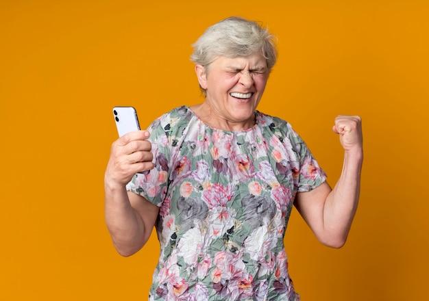 De gelukkige oudere vrouw heft de telefoon van de vuistholding op die op oranje muur wordt geïsoleerd