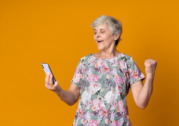De gelukkige oudere vrouw heft vuist op en bekijkt telefoon die op oranje muur wordt geïsoleerd