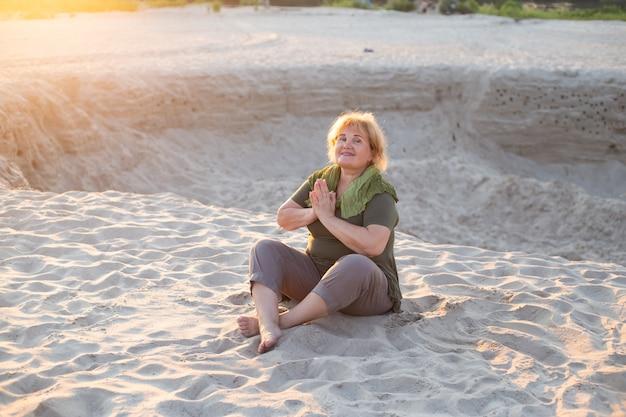 De gelukkige oudere vrouw mediteert buiten op een zand in de zomer