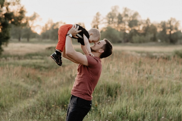 De gelukkige papa en de zoon glimlachen en spelen op gebied bij zonsondergang