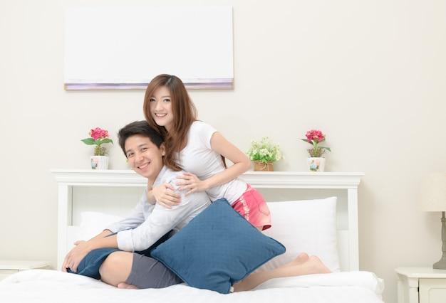 De gelukkige paren glimlachen en zitten op bed,