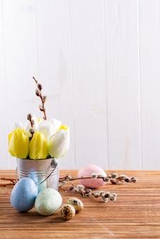 De gelukkige pasen-kaart met verse de lentetulpen bloeit in een emmer en met de hand gemaakte geschilderde eieren op een houten lijst.