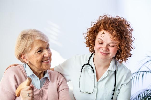 De gelukkige patiënt houdt verzorger voor een hand terwijl samen tijd doorbrengen. bejaarde vrouw in verpleeghuis en verpleegster.