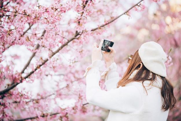 De gelukkige reisvrouw en neemt een foto van de kers van sakura bloeit boom op vakantie terwijl de lente