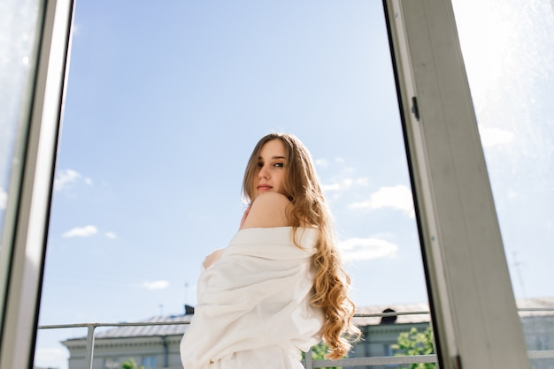 De gelukkige rijke jonge vrouw draagt een nachtjas bij het grote raam in de slaapkamer, kijk naar buiten en geniet van de droom van het uitzicht