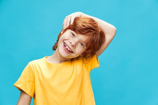 De gelukkige roodharige jongen hield zijn hoofd schuin en houdt zijn hand dichtbij zijn gezicht op blauw