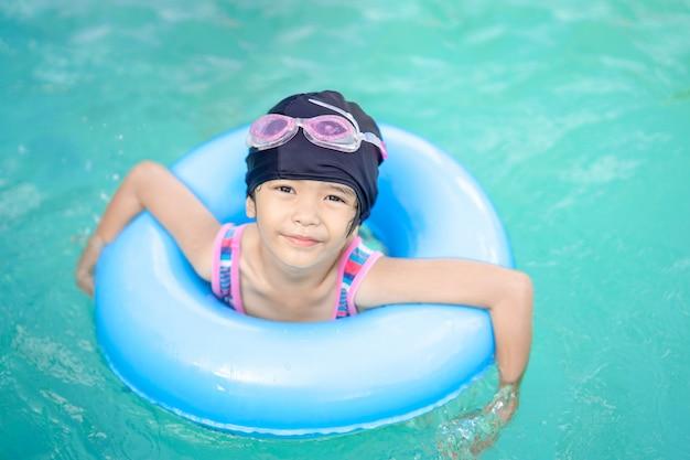 De gelukkige slaap van het jonge geitjesmeisje op de veiligheid van de het levensring voor het zwemmen in zwembad