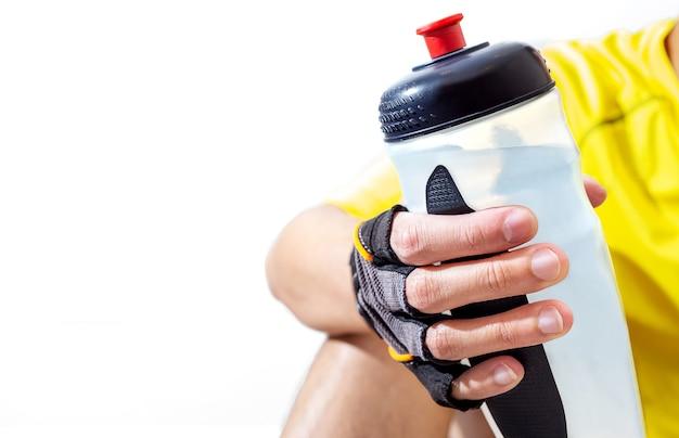 De gelukkige sportman drinkt water in huiswoonkamer voor hardlopen, joggen en trainen in de fitnessruimte