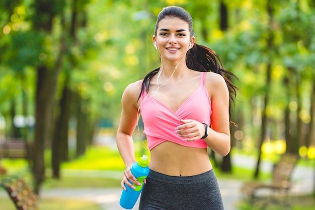 De gelukkige sportvrouw die in het park loopt